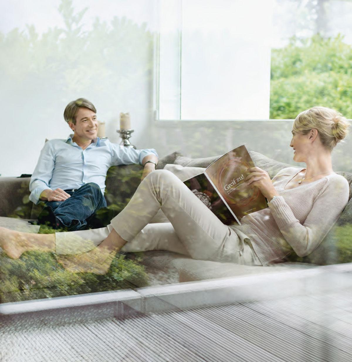 Bild durch Fenster wo Frau und Mann eine Unterhaltung auf Sofa führen