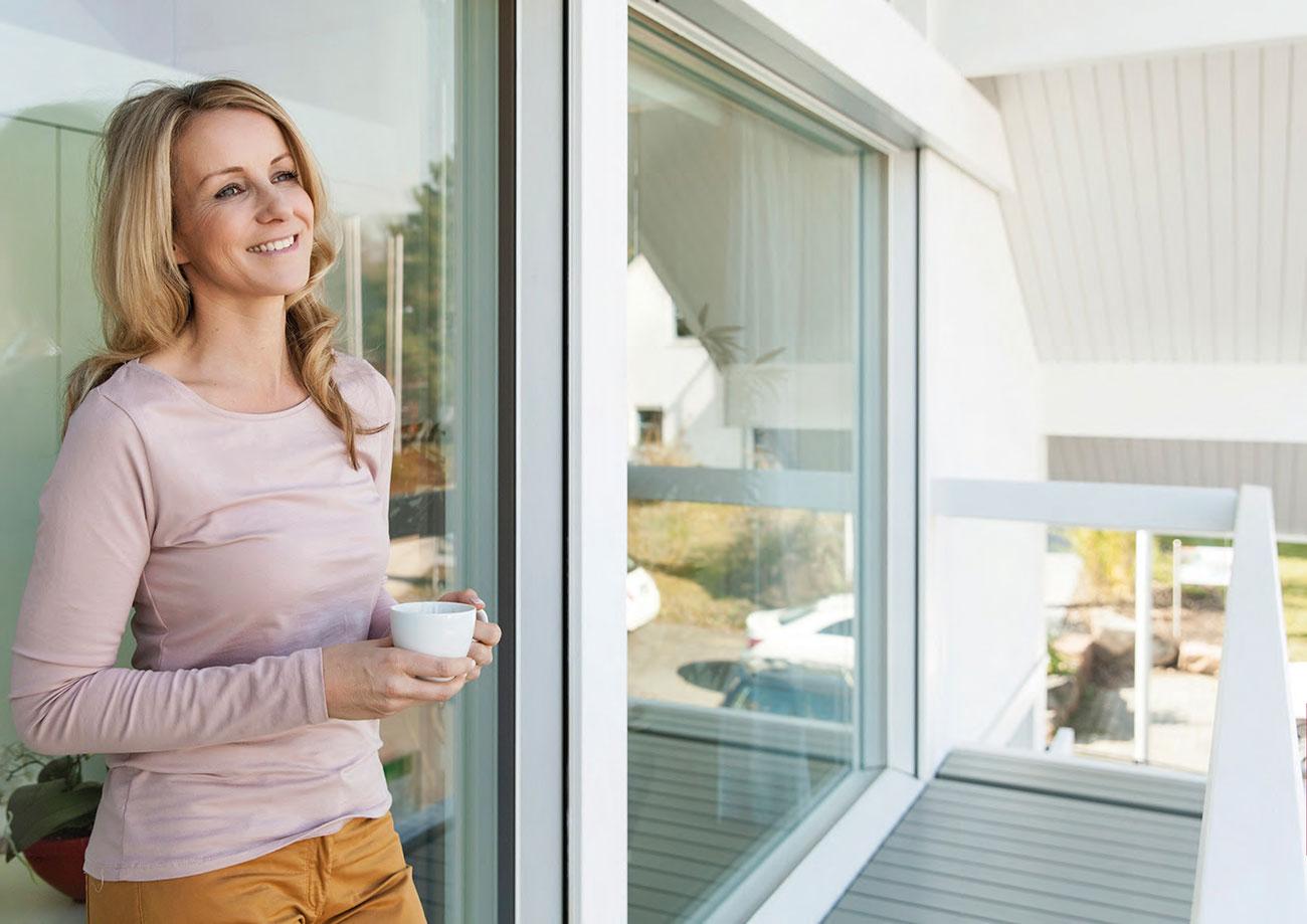 Frau angelehnt an Kunststofffenster in weiß der Marke Schüco von Ottis Fenster und Türen