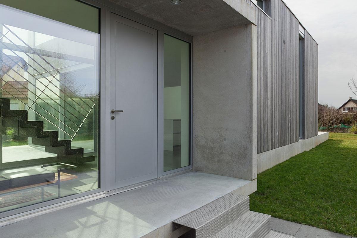 Hellgraue Eingangstür aus Aluminium und Holz