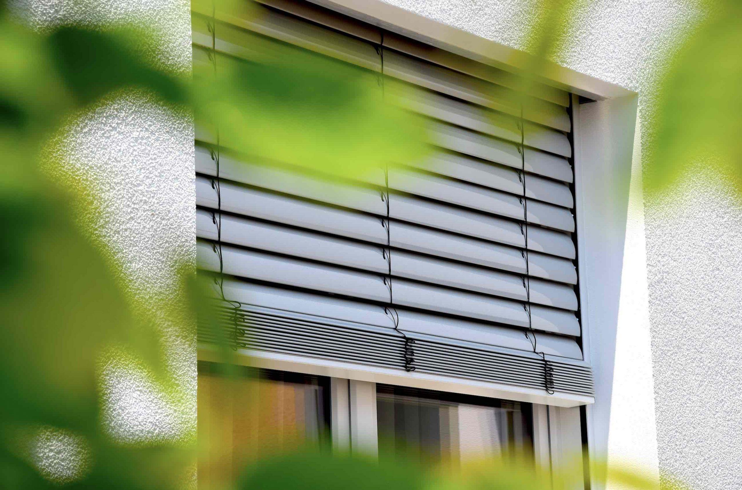 Rolladen Raffstore am Fenster als Sonnenschutz