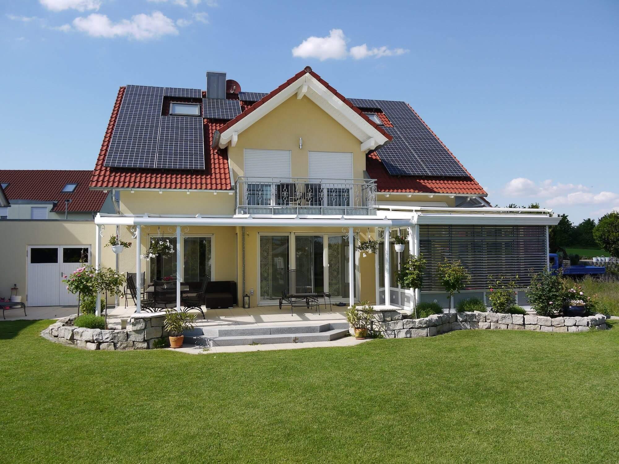Terrassendach der Marke WiPro mit Außenblick vom Garten auf das Haus von Ottis Fenster und Türen